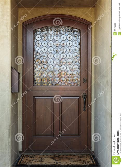 Wooden Front Door Of Home With Ornate Glass Detail Stock
